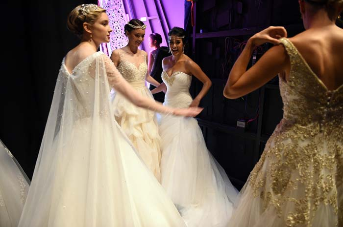 NEW YORK, NY - OCTOBER 07: Models prepare backstage during 2016 Alfred Angelo Disney Fairy Tale Weddings Bridal Collection fashion show debut at New Amsterdam Theatre on October 7, 2015 in New York City. (Photo by Bryan Bedder/Getty Images for Alfred Angelo)